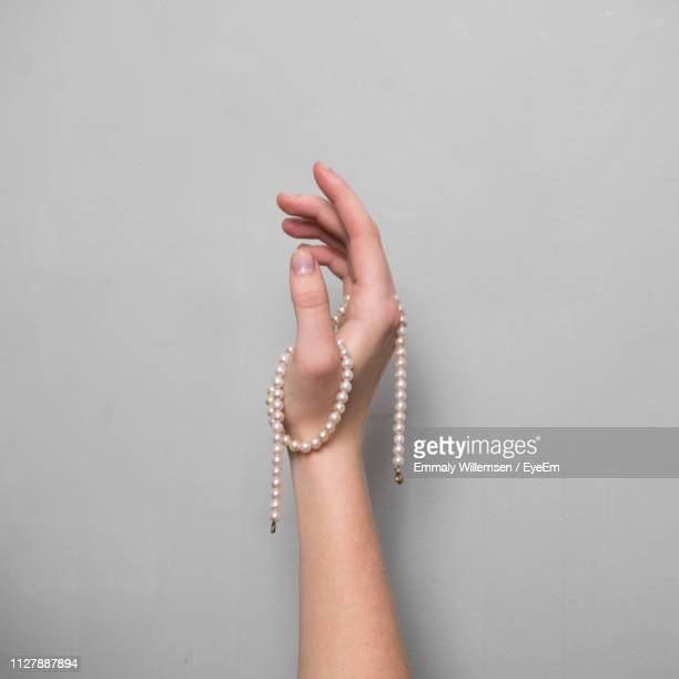 close-up of woman hand with pearl necklace against gray background - pearl jewelry stock pictures, royalty-free photos & images