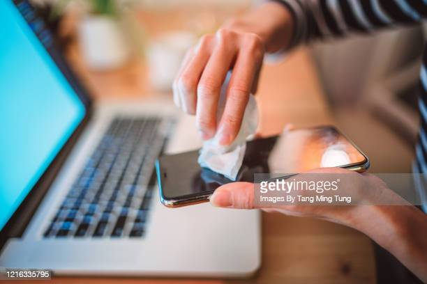 close-up of woman hands cleaning the surface of a smartphone with disinfectant wipe at home - aplanar a curva imagens e fotografias de stock