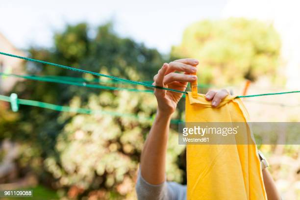 close-up of woman hanging up yellow blanket on clothesline - washing stock pictures, royalty-free photos & images