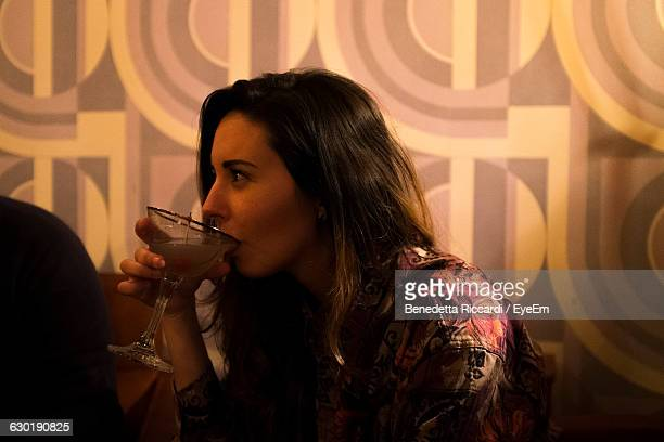 Close-Up Of Woman Having Cocktail Against Wall At Restaurant