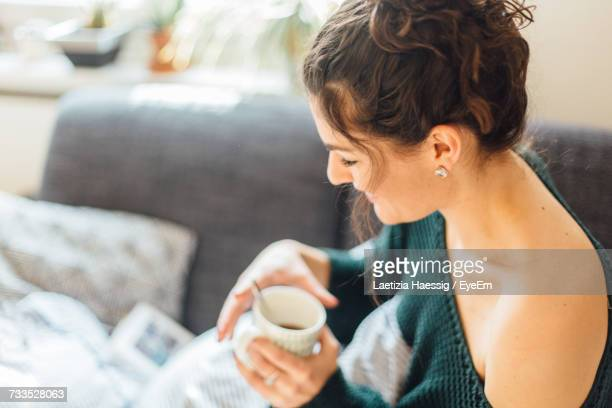 close-up of woman having coffee while sitting on bed at home - off shoulder stock pictures, royalty-free photos & images