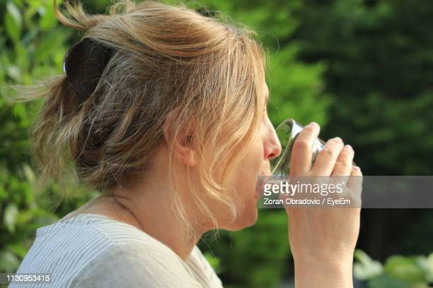 Close-Up Of Woman Having Drink Against Plants