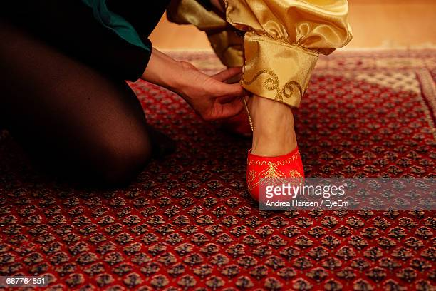 Close-Up Of Woman Helping Bride In Wearing Shoe