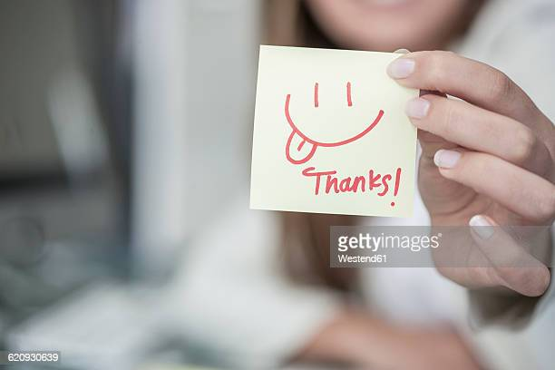 Close-up of woman holding a sticky note with a smiley face