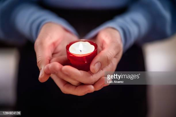 close-up of woman holding a votive candle - candle stock pictures, royalty-free photos & images
