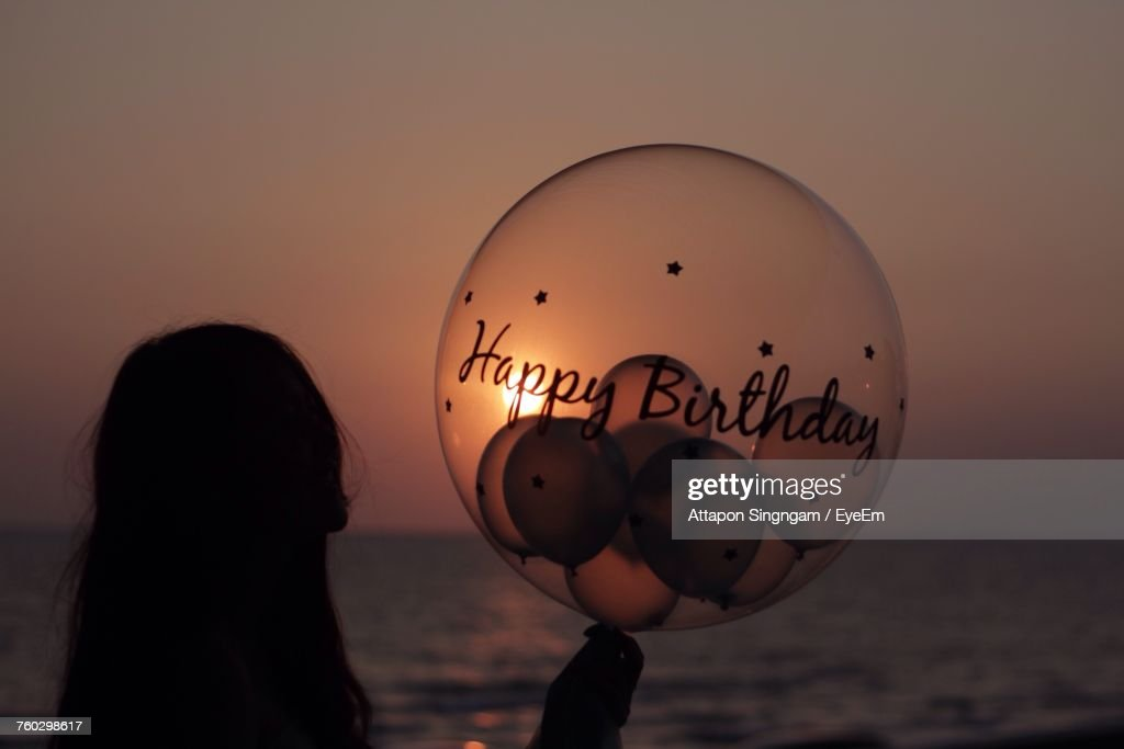 Close-Up Of Woman Holding Balloons On Beach Against Sky During Sunset : Stock Photo
