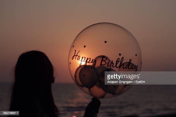 Close-Up Of Woman Holding Balloons On Beach Against Sky During Sunset