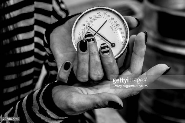 Close-Up Of Woman Holding Barometer
