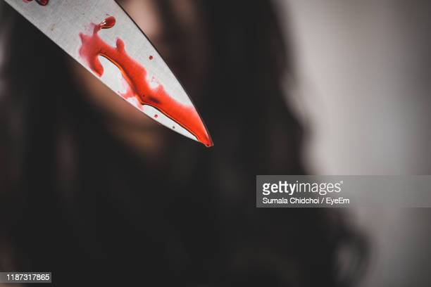 close-up of woman holding blood covered knife - weapon stock pictures, royalty-free photos & images