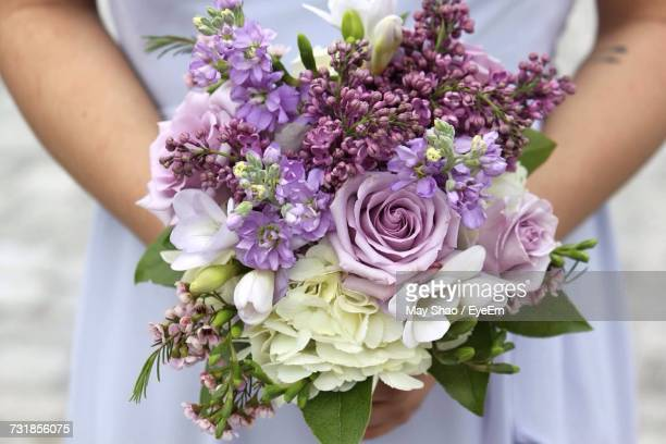 close-up of woman holding bouquet - purple roses bouquet ストックフォトと画像