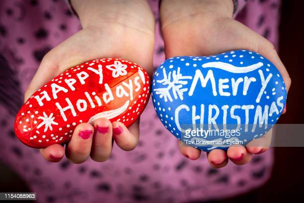 close-up of woman holding christmas decorations - happy holidays stock photos and pictures