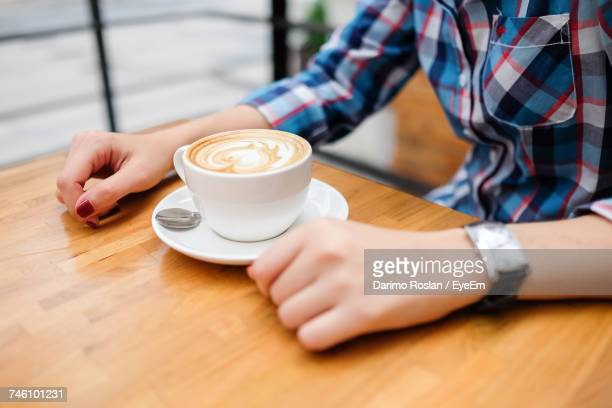 close-up of woman holding coffee cup - mocha stock photos and pictures