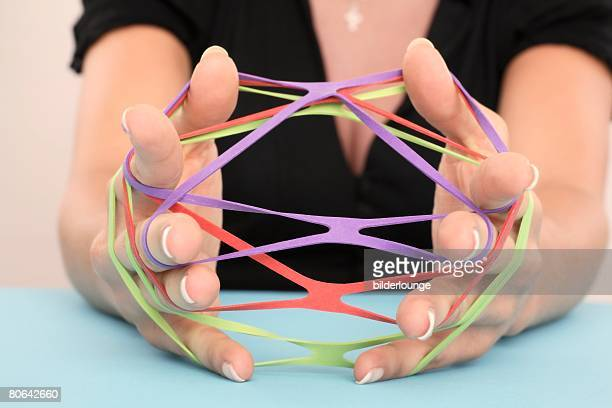 close-up of woman holding colourful rubber bands