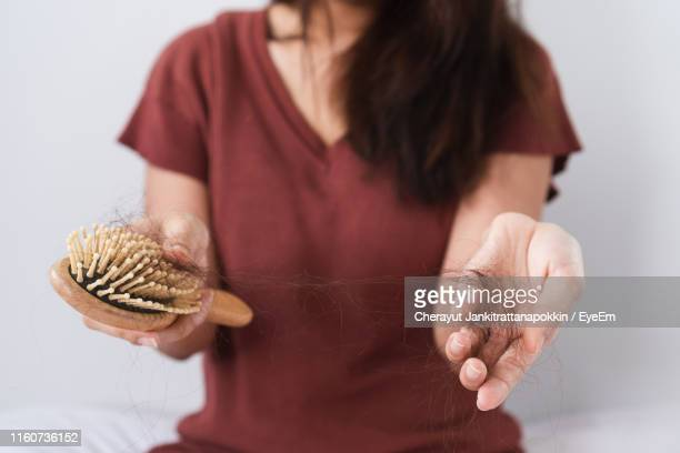 close-up of woman holding comb and hair at home - penteando imagens e fotografias de stock