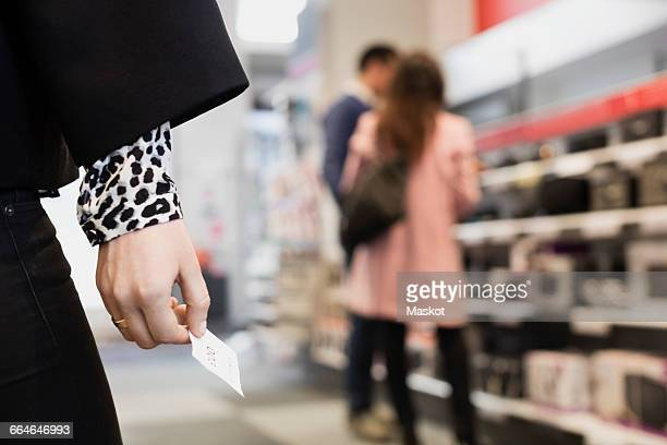 Close-up of woman holding coupon with salesman and customer standing in background at store