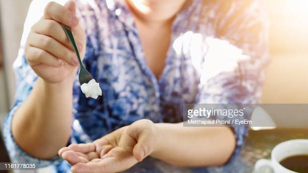 close-up of woman holding cream - metthapaul stock photos and pictures