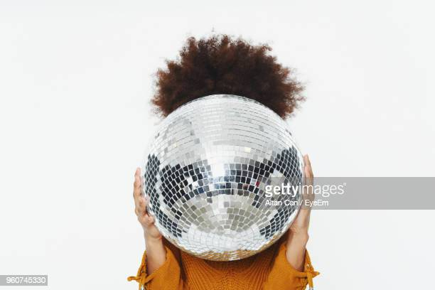 close-up of woman holding disco ball against white background - mirror ball stock pictures, royalty-free photos & images