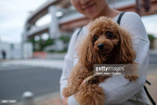 Close-Up Of Woman Holding Dog