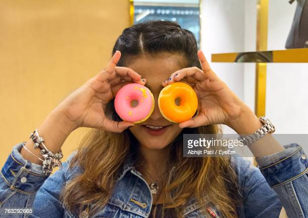 Close-Up Of Woman Holding Donuts In Front Of Eyes