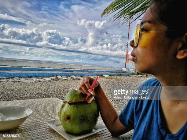 close-up of woman holding drink at beach against sky - negros oriental stock pictures, royalty-free photos & images