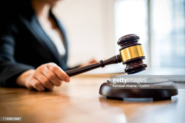 close-up of woman holding gavel on table - gavel stock pictures, royalty-free photos & images