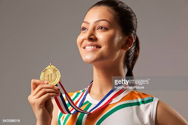 Close-up of woman holding gold medal isolated over gray background