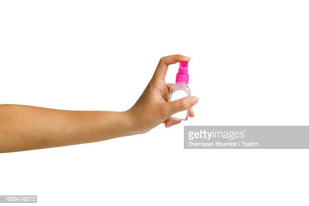 close-up of woman holding hand sanitizer against white background - hand sanitizer stock pictures, royalty-free photos & images