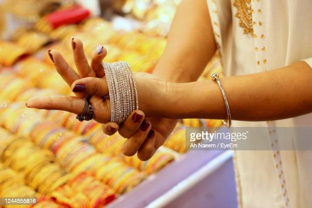 close-up of woman holding hands - bangle stock pictures, royalty-free photos & images