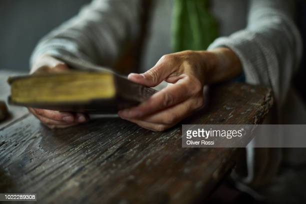 close-up of woman holding historical book - bible stock pictures, royalty-free photos & images