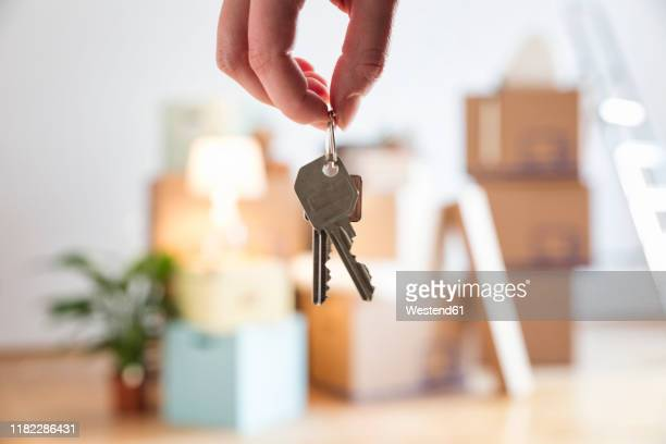 close-up of woman holding house key in new home - new home stock pictures, royalty-free photos & images