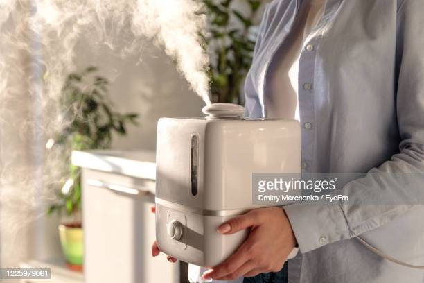 close-up of woman holding humidifier - humidifier stock pictures, royalty-free photos & images