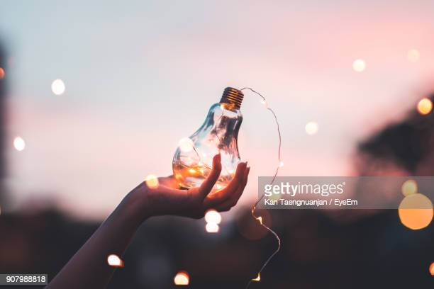 close-up of woman holding illuminated light bulb against sky at night - light bulb stock pictures, royalty-free photos & images
