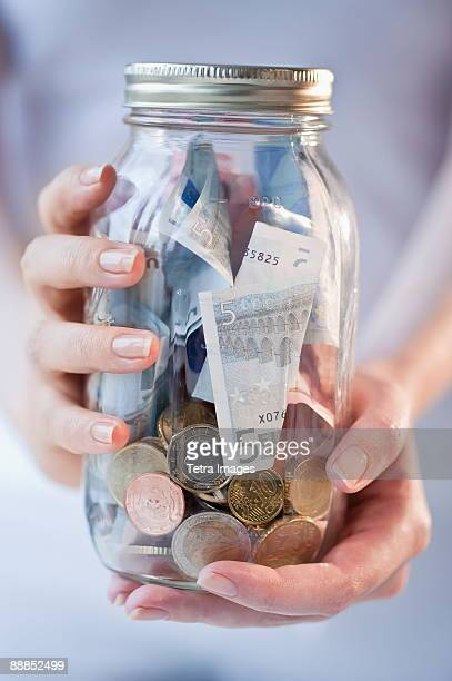 Close-up of woman holding jar of money