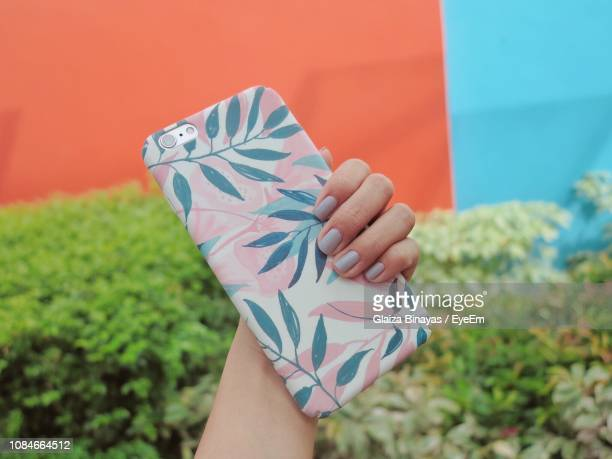 close-up of woman holding mobile phone - phone cover stock pictures, royalty-free photos & images