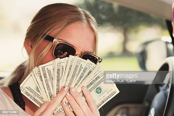 Close-Up Of Woman Holding Money In Car
