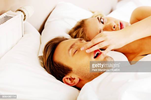 Close-Up Of Woman Holding Nose Of Snoring Man At Home