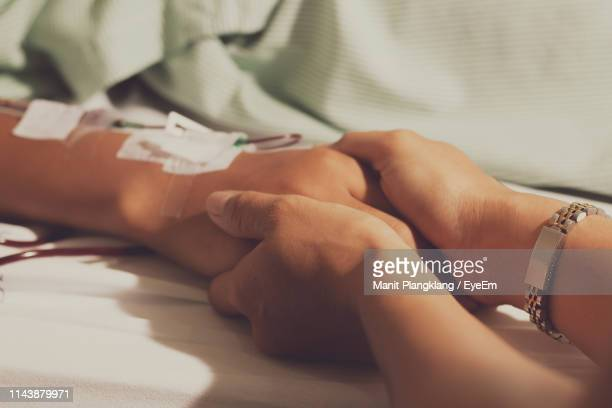 close-up of woman holding patient hand lying on bed at hospital - iv drip womans hand stock pictures, royalty-free photos & images