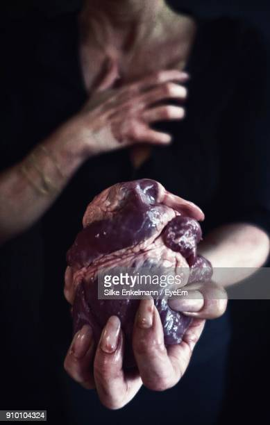 Close-Up Of Woman Holding Pig Heart Holding Against Black Background