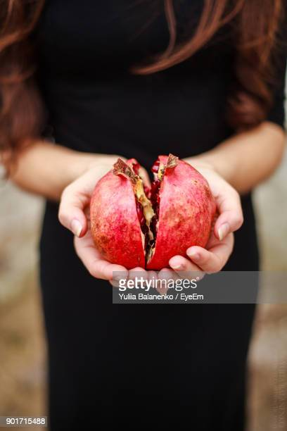 close-up of woman holding pomegranate - tropische frucht stock-fotos und bilder