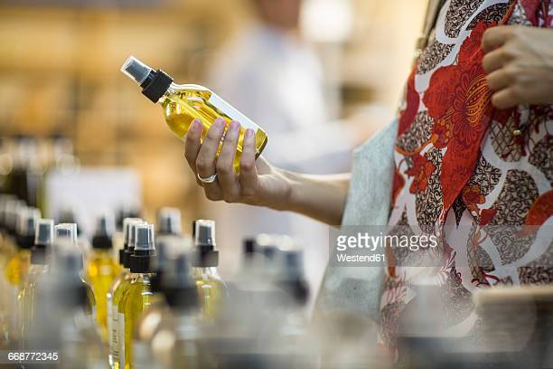 Close-up of woman holding scent bottle in shop