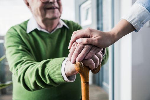 Close-up of woman holding senior man's hand leaning on cane - gettyimageskorea