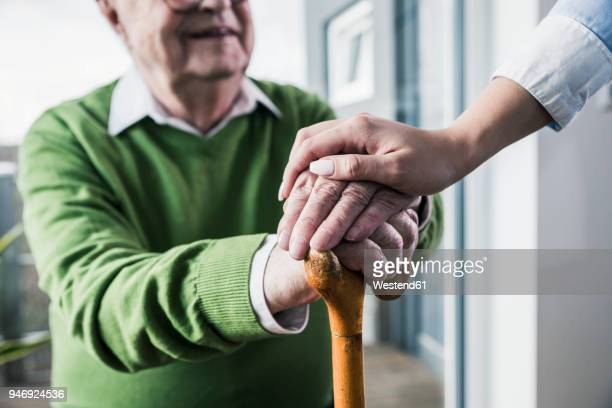 close-up of woman holding senior man's hand leaning on cane - ermutigung stock-fotos und bilder
