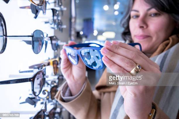 Close-Up Of Woman Holding Sunglasses At Store