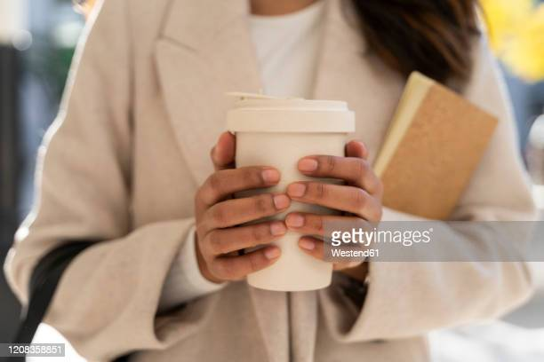 close-up of woman holding takeaway coffee - hot spanish women stock pictures, royalty-free photos & images