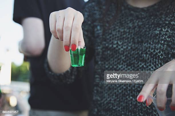 Close-Up Of Woman Holding Tequila Shot