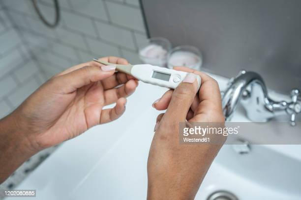 close-up of woman holding thermometer in bathroom - digital thermometer ストックフォトと画像