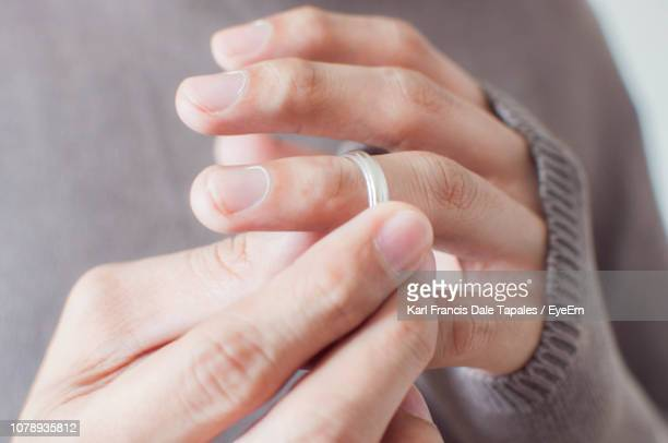 close-up of woman holding wedding ring - absence stock pictures, royalty-free photos & images