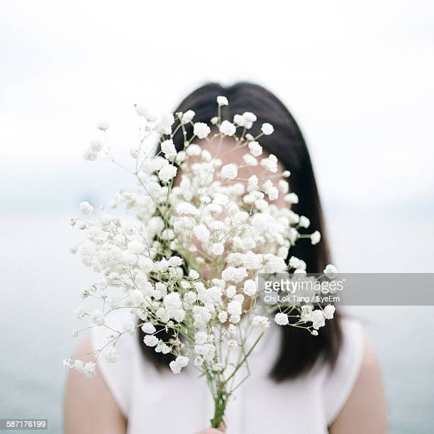Close-Up Of Woman Holding White Flowers