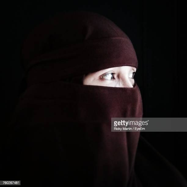 close-up of woman in burka looking away against white background - burka photos et images de collection