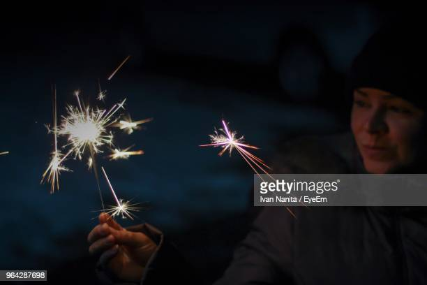 Close-Up Of Woman In Fur Coat Holding Lit Sparkler At Night